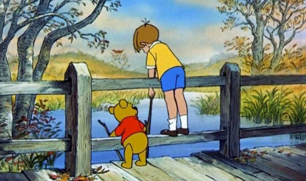 Animated Characters Winnie the Pooh (teddy bear) and Christopher Robin holding sticks over a bridge